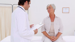 Smiling patient talking with her serious doctor Footage