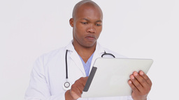 Serious doctor standing while holding a tablet pc Footage