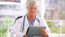 Smiling doctor using a tablet computer Stock Video Footage