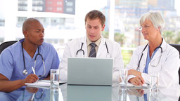 Mature doctor sitting with her team while looking Stock Video Footage