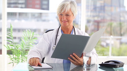 Smiling mature doctor looking at documents Live Action