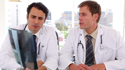 Serious doctors looking together at an xray Stock Video Footage