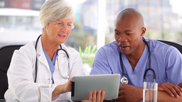 Happy doctors working with a touchscreen Stock Video Footage