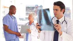 Smiling doctor looking at a chest xray Stock Video Footage