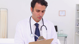 Serious doctor holding his professional clipboard Stock Video Footage