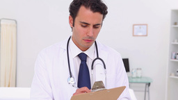 Serious doctor holding his professional clipboard Footage