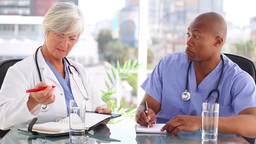 Nurse and doctor writing while working together Stock Video Footage