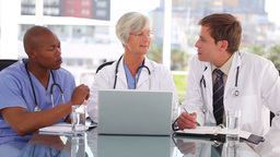 Smiling mature doctor sitting with colleagues in f Stock Video Footage