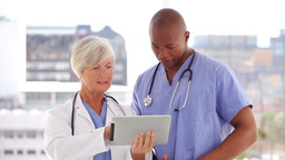 Happy doctor and nurse looking at a tablet pc Footage