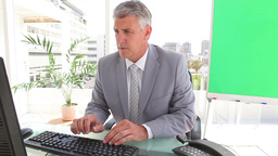 Businessman typing on a keyboard before looking at Footage