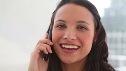 Woman smiling as she talks on the phone Footage