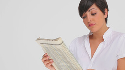 Businesswoman nods as she reads a newspaper Footage