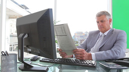 Businessman smiling as he reads a newspaper Stock Video Footage