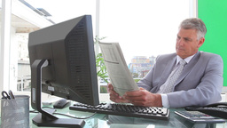Businessman smiling as he reads a newspaper Footage