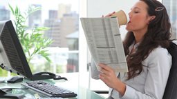 Businesswoman reading a newspaper while drinking c Footage