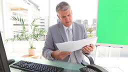 Businessman looking at pages of statistics Footage