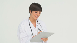 Happy doctor writing on a clipboard Stock Video Footage