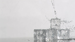 Trickle of water in a super slow motion flowing on ice cubes and falling it Footage