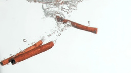 Three cinnamon sticks in a super slow motion falli Stock Video Footage