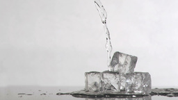 Water falling in super slow motion onto ice cubes Footage