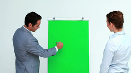 Businessman explaining something on a board to a c Footage