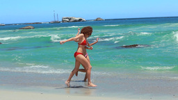 Two Women Running Together On The Beach Shore stock footage
