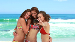 Three women taking a group photo at the beach Footage