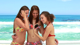 Three women taking a group photo at the beach Stock Video Footage