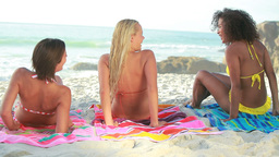 Three women sitting down on their towels Footage