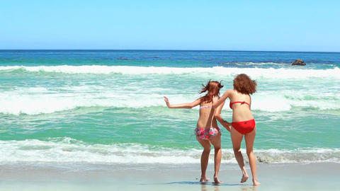 Two women in bikinis playing in the sea Stock Video Footage