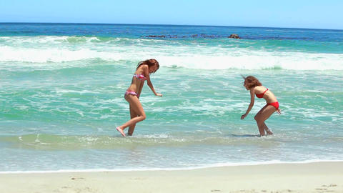 Two women in bikinis playing in the sea Stock Video Footage