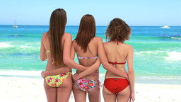 Three girls in bikinis staring out at the water Stock Video Footage
