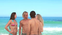 Friends chatting to each other at the beach Stock Video Footage