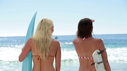 Two surfer women check out the ocean Stock Video Footage
