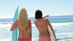Two female surfers with boards at the beach Stock Video Footage