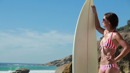 Woman wearing sunglasses with a surfboard in hand Stock Video Footage