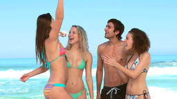 Two women and a man together at the beach Footage