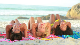 Three women sitting together on the beach Stock Video Footage