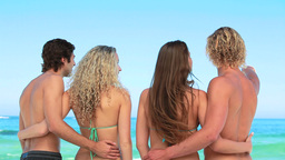 Four friends embracing one another at the beach Footage