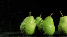Green pears in super slow motion being soaked Footage