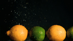 Limes and lemons in super slow motion receiving wa Footage