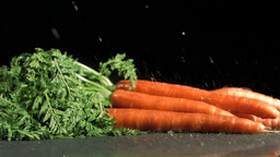 Carrots in super slow motion receiving raindrops Footage