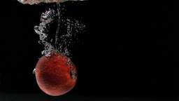 Red apple in super slow motion falling in the wate Stock Video Footage