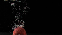 Red apple in super slow motion falling in the wate Footage