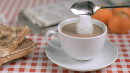 Sugar poured in super slow motion into white coffe Stock Video Footage
