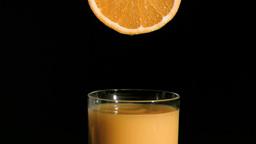 Orange drop falling in super slow motion in a glas Footage