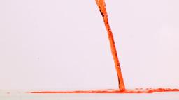 Orange liquid flowing in super slow motion on a gr Footage
