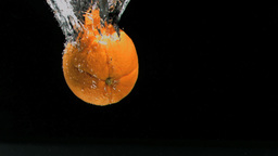 Orange diving in super slow motion in water Footage