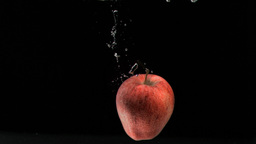 Apple rotating in super slow motion into water Footage