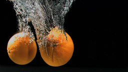 Two oranges falling in super slow motion Footage